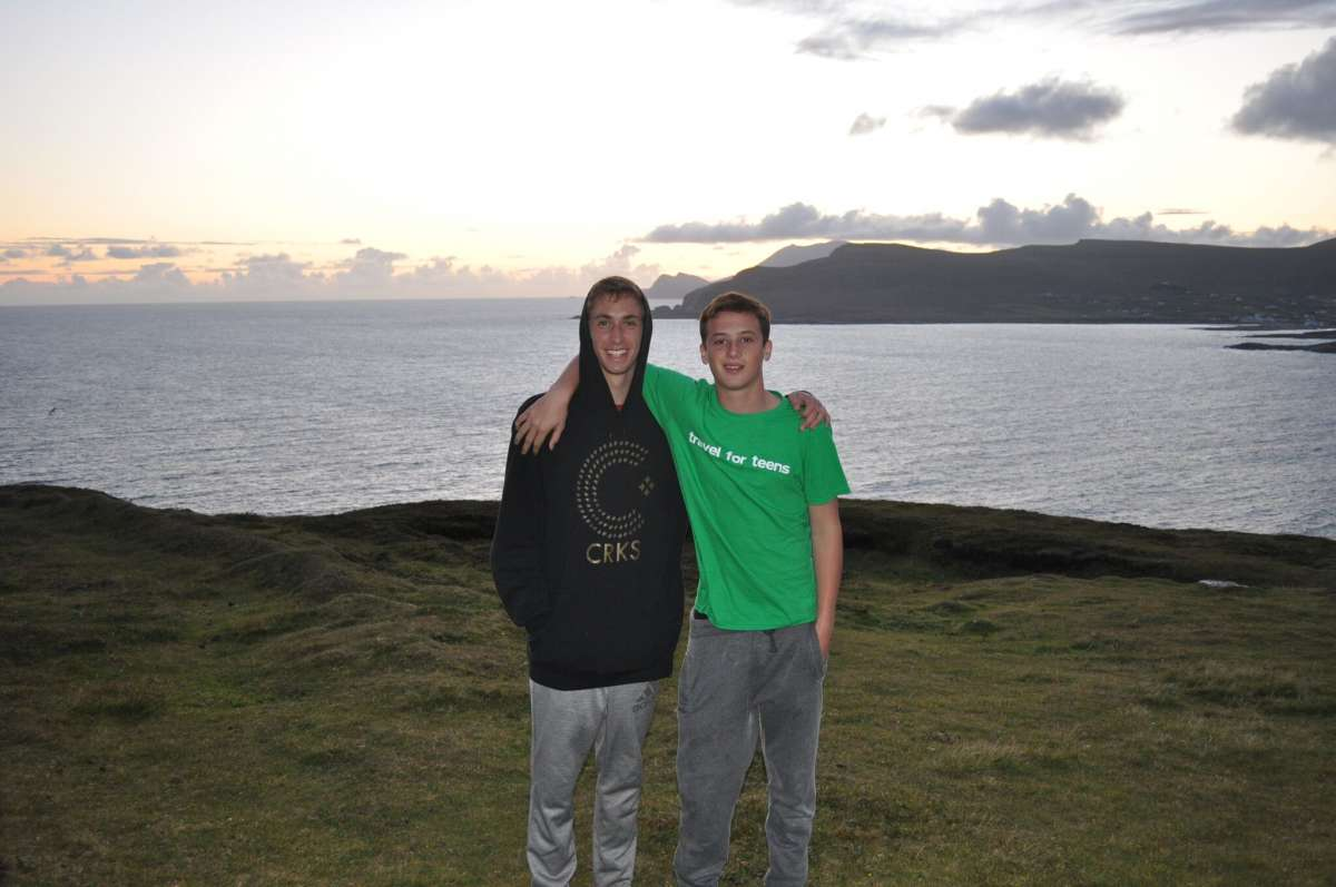 Teenage travelers walk through rolling green hills of Ireland on summer youth travel program