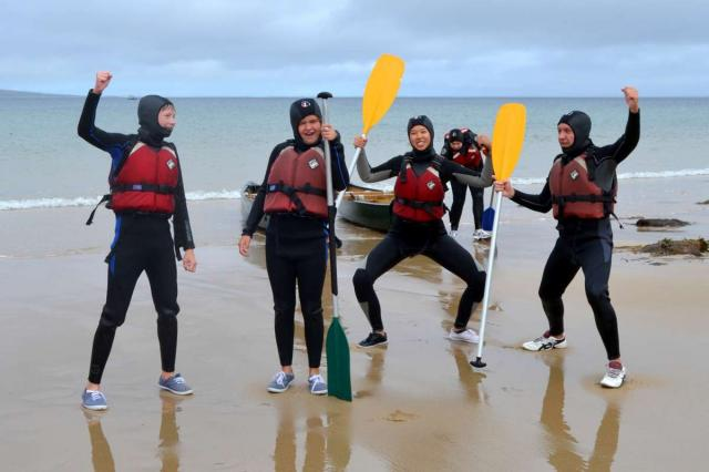 Teenage travelers sea canoeing in Ireland on summer youth adventure travel program