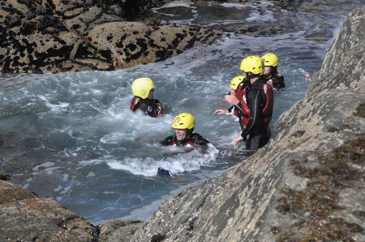 Teenage travelers coasteering on summer youth adventure travel program in Ireland