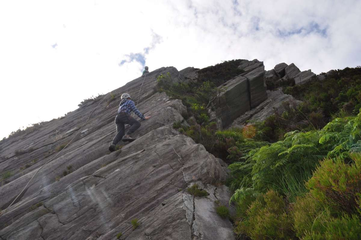 Teenage travelers climb rock faces in Ireland on summer youth adventure travel program