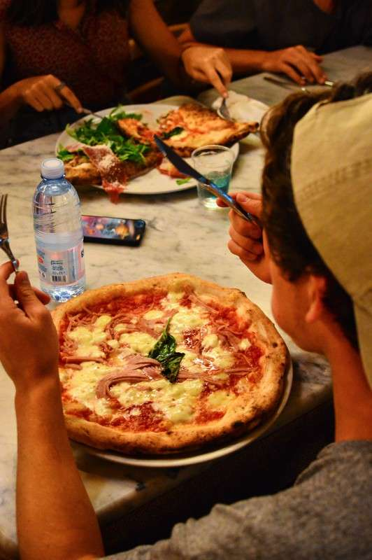 High school teen enjoys authentic pizza in Italy on their summer tour.