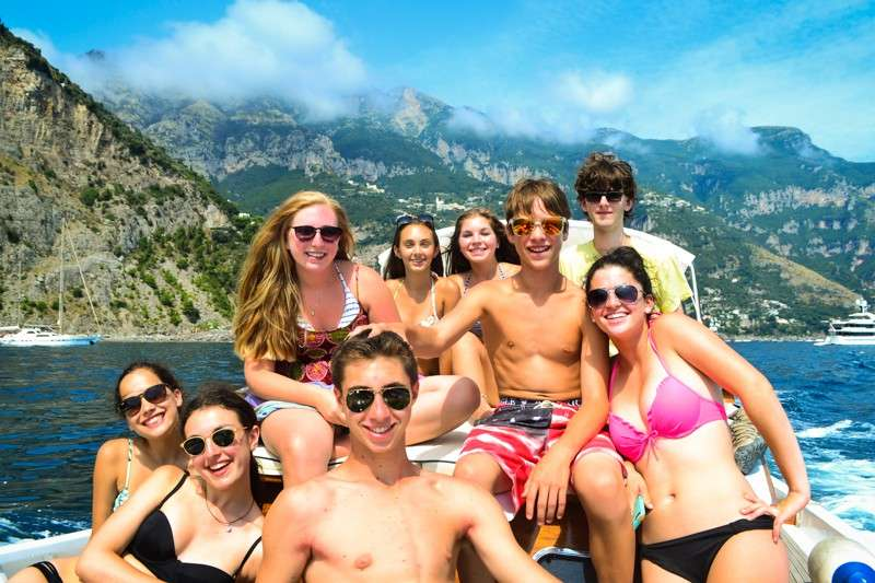 High school students smile on the private boat cruise along Amalfi Coast in Italy.