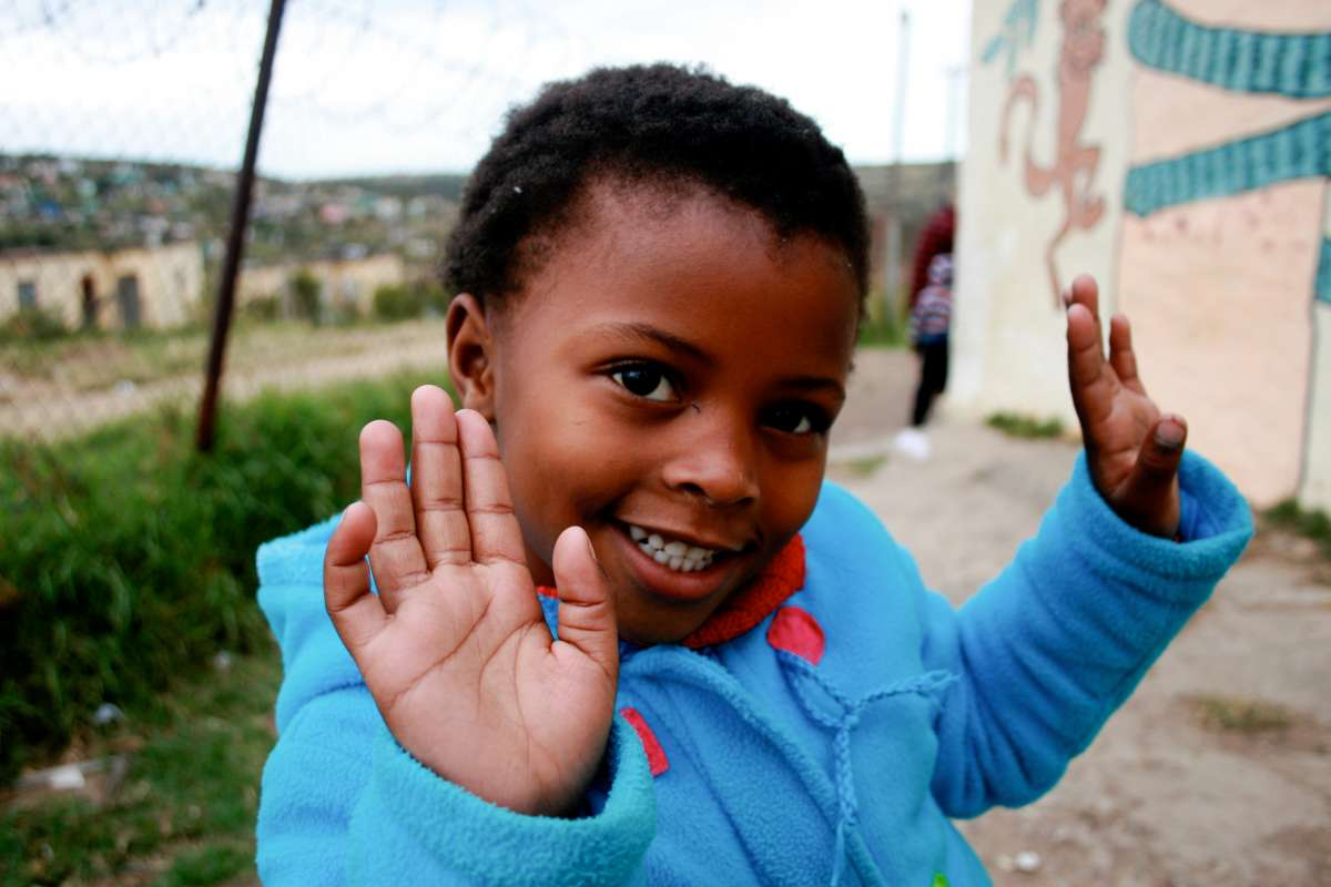 A local child poses for a photo for teens on summer service and safari program in South Africa.
