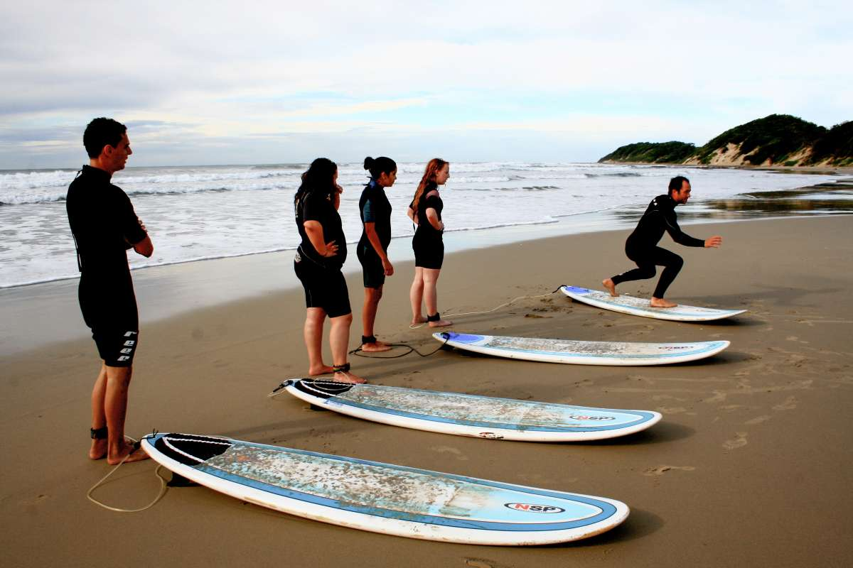 Group of teens learns how to surf in South Africa on summer service and safari adventure program.