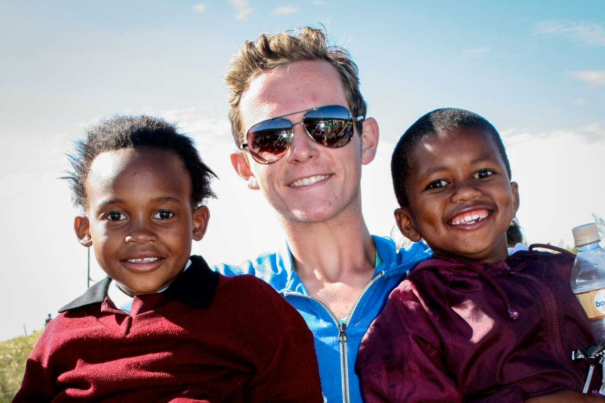 Teen boy plays with local kids on service and safari summer program in South Africa.