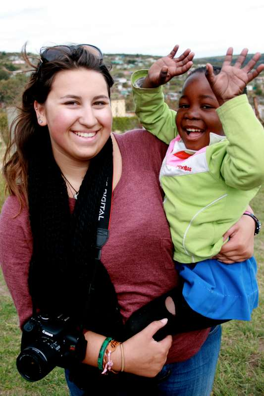 Teen plays with local child as part of service and safari program in South Africa.