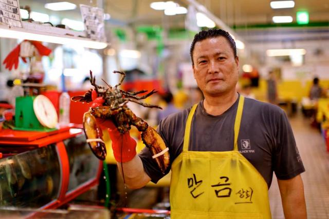 Local seafood vendor at Jagalchi fish market seen on summer teen travel program in Busan