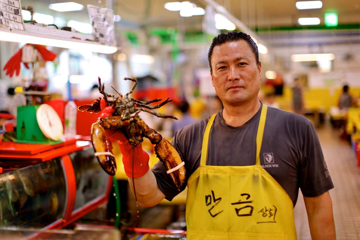 Local seafood vendor at Jagalchi fish market seen on summer teen travel program in Busan