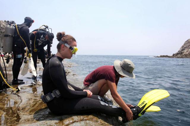 Teenage traveler prepares to scuba dive at Jeju Island during summer teen travel program in South Korea