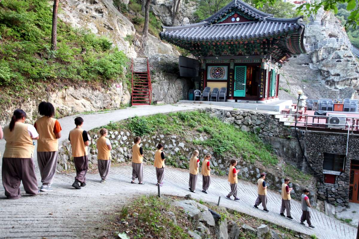 Teenage travelers do morning walking meditation at Golgulsa Temple during overnight stay while on summer teen travel program