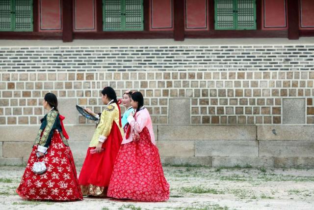 Local Korean women seen wearing hanbok outside Gyeongbukgong Palace in Seoul on summer youth travel program