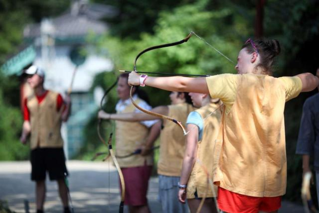 Teenage travelers learn traditional archery at Golgulsa Temple during temple stay experience on summer youth travel program