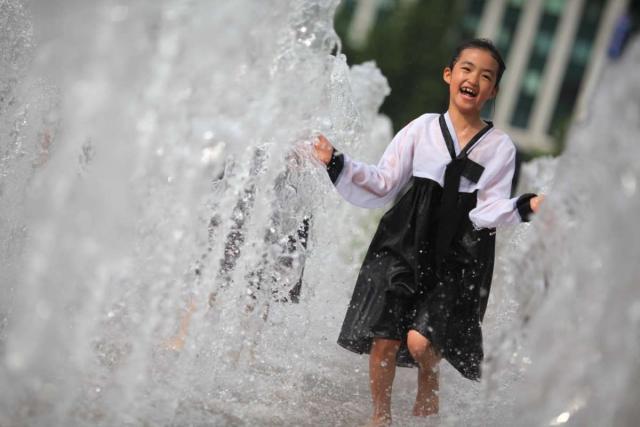 Korean girl runs through water fountains at Seoul City Hall seen on summer teen travel program