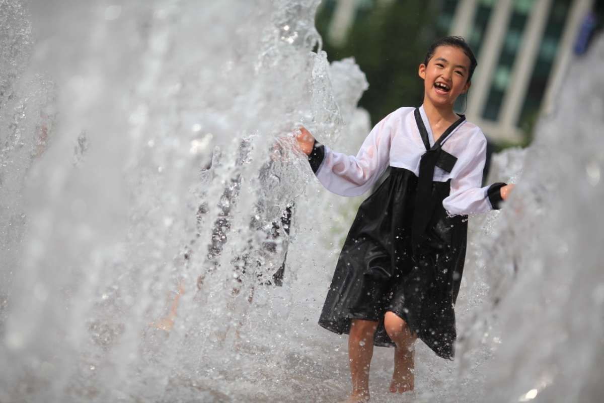 Korean girl runs through water fountains at Seoul City Hall seen on summer teen travel program