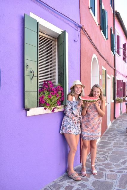 Teenage travelers eat watermelon on Venice island of Murano during summer travel photography program