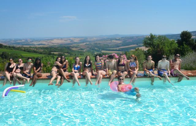 Teen travelers relax in Tuscany vineyard pool during summer photography program in Italy