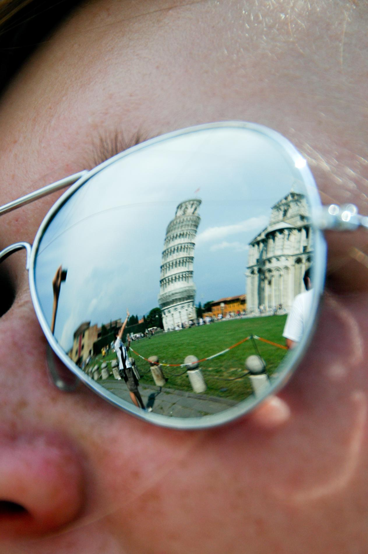 Leaning Tower of Pisa reflected in teenage traveler's sunglasses on summer travel photography program