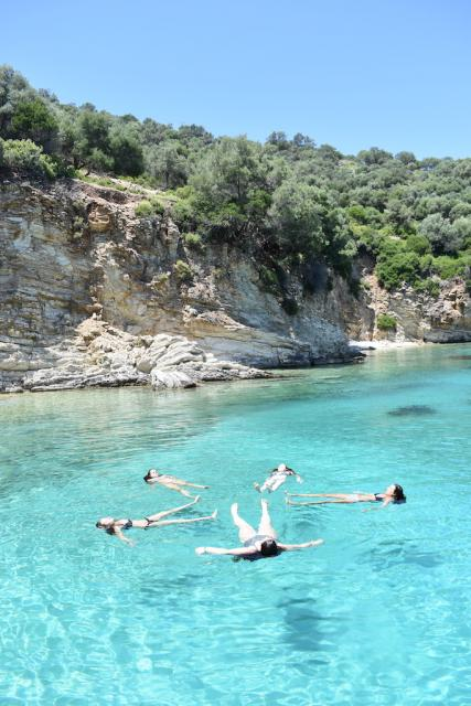 Teenage travelers swim in Mediterranean Sea during summer youth travel program in Greece