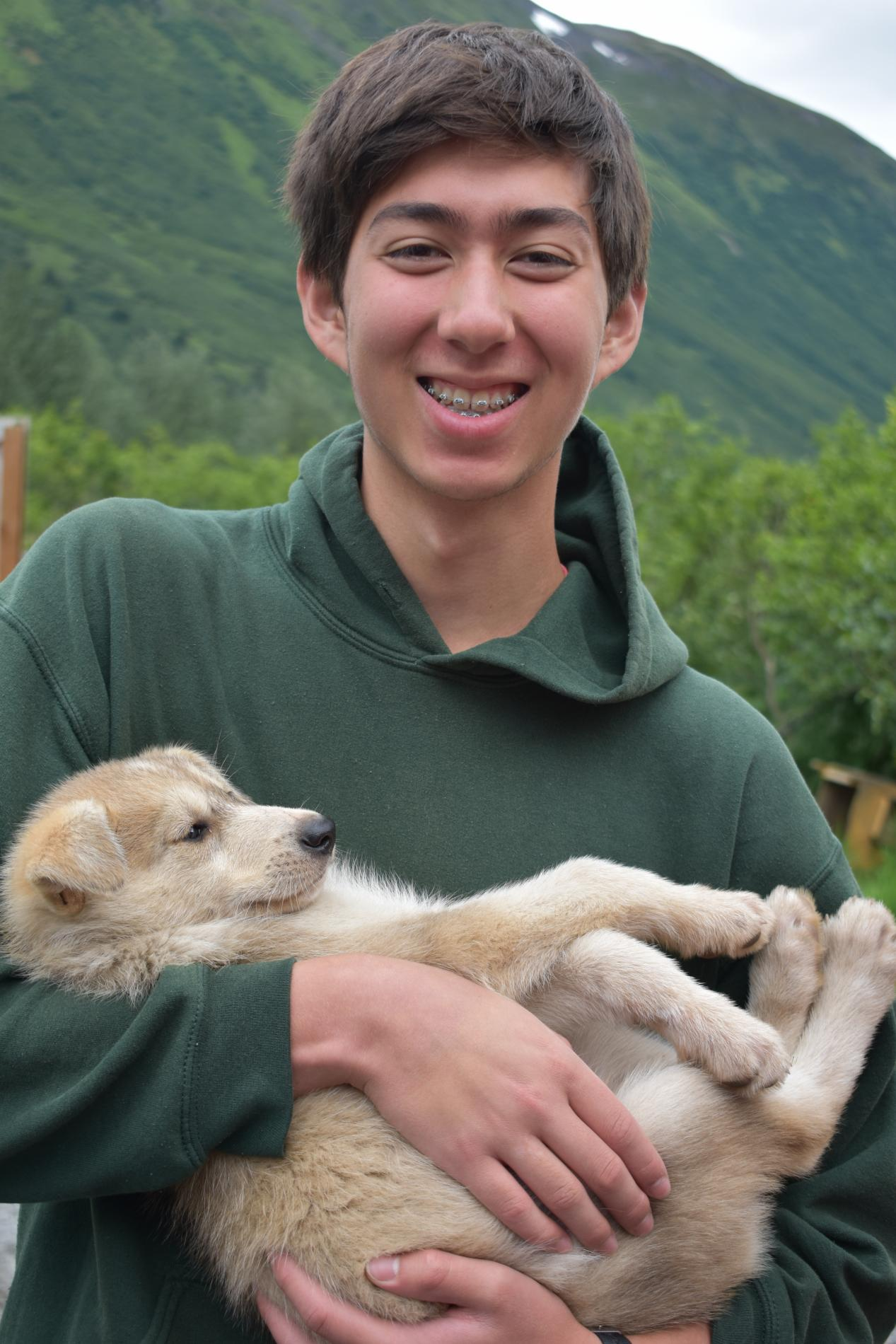 Teen boy holds a puppy on summer service and adventure program in Alaska.