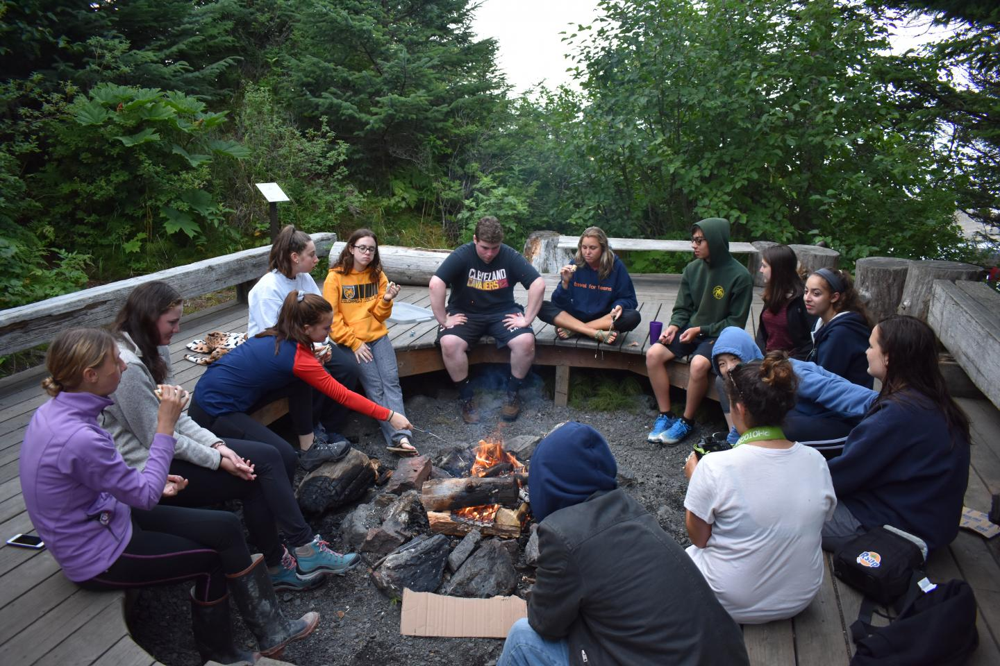 Teens hang out by the fire on service and adventure program in Alaska.