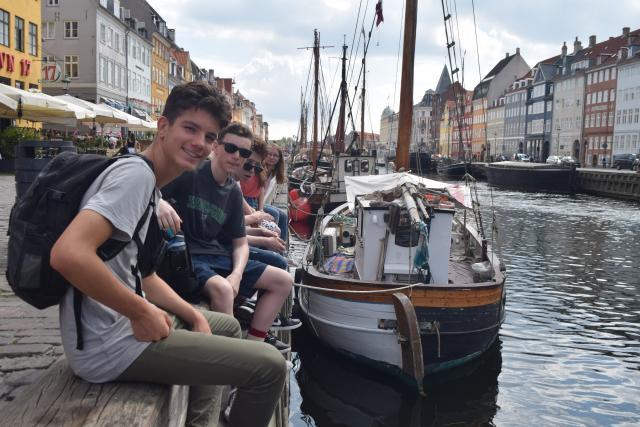 American teenage travelers at Copenhagen's Nyhavn harbor during summer youth travel program in Scandinavia
