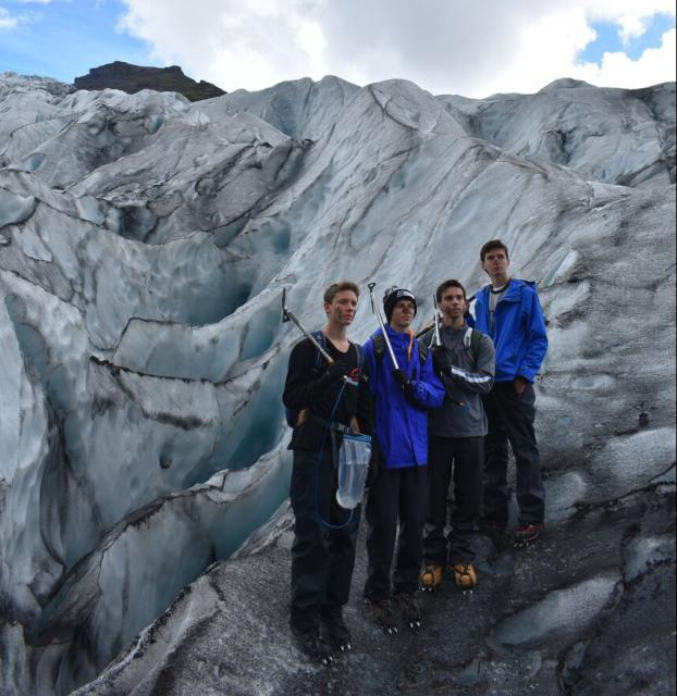 Teenage travelers do glacier hike during summer youth travel program in Scandinavia