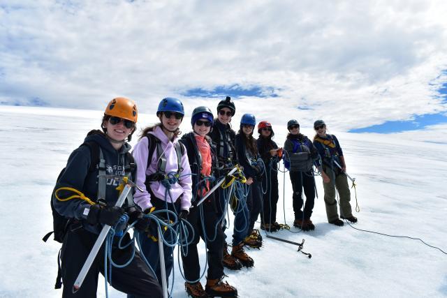 Teenage travelers go on glacier hike during summer youth travel program in Scandinavia