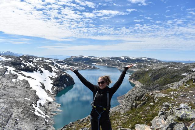 Teenage traveler admires scenic views of Norwegian fjords during summer youth travel program in Scandinavia