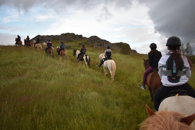 Teenage travelers ride Icelandic horses during summer youth travel program in Scandinavia