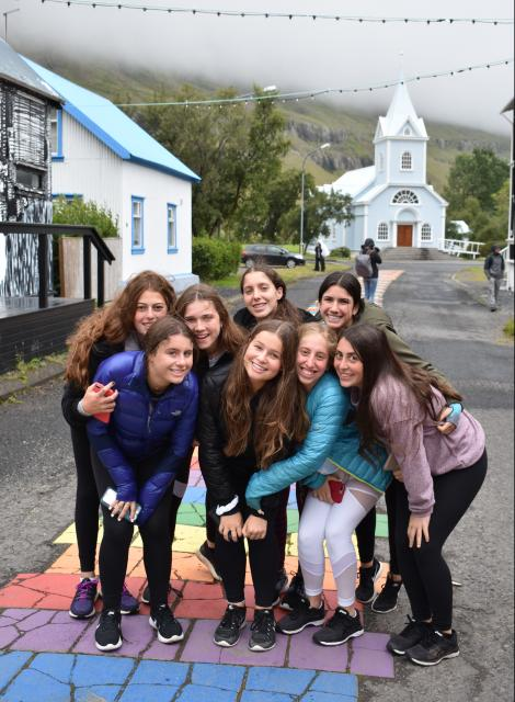 Teenage travelers visit small Iceland town of Seydisfjordur during summer youth travel program in Scandinavia
