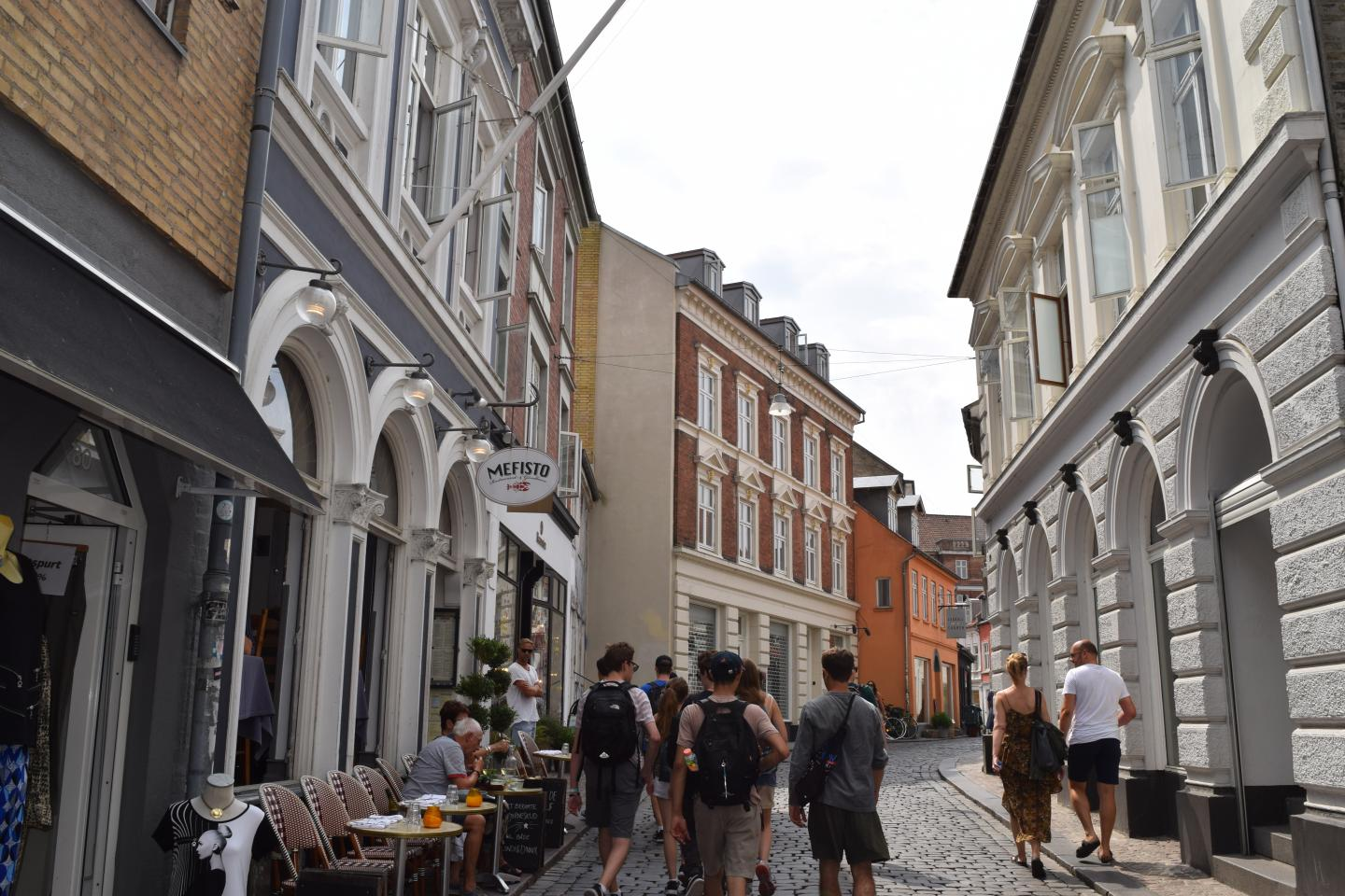Teenage travelers explore small cobblestone streets during summer youth travel program in Scandinavia