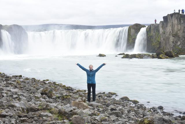 Teenage traveler poses with waterfall during summer youth travel program in Scandinavia