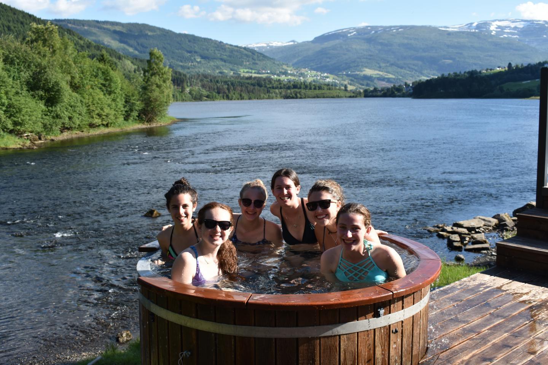 Teenage travelers soak in hot tub during summer youth travel program in Scandinavia