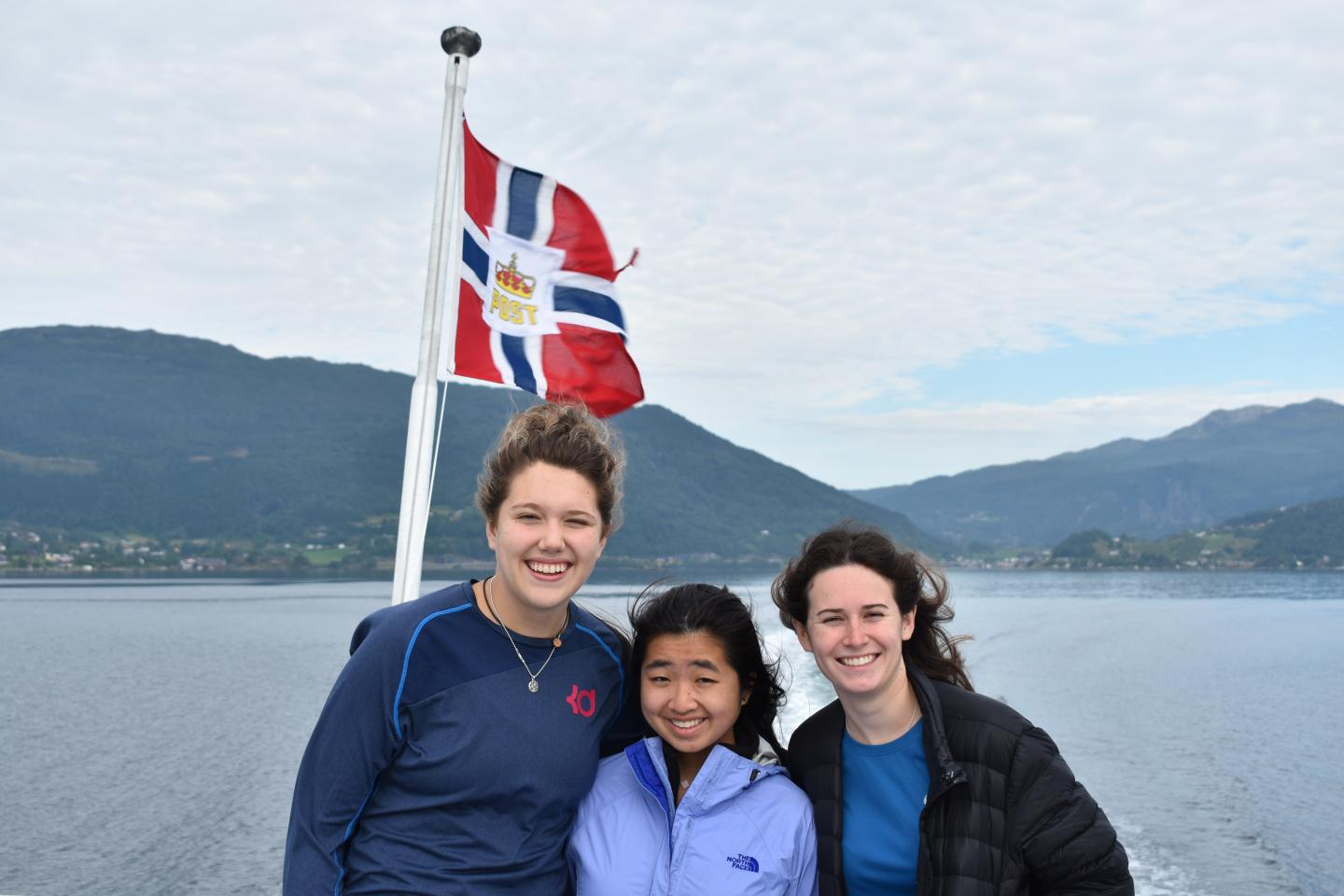 Teenage travelers sailing on a boat cruise in Norwegian fjords during summer youth travel program in Scandinavia