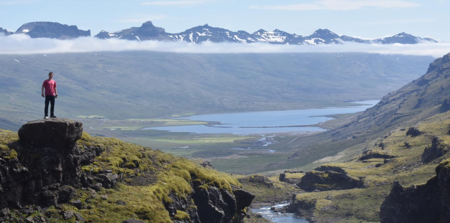 High school student poses in the dramatic landscape of Iceland during their summer teen tour