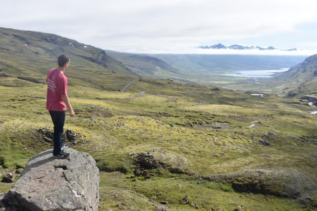 Teenage traveler looks out over views of Iceland landscape during summer youth travel program in Scandinavia