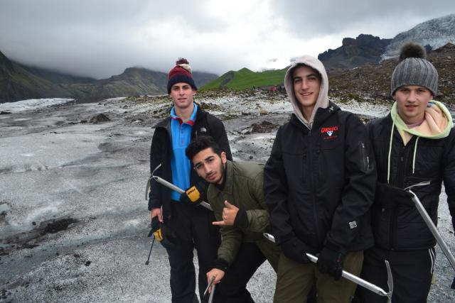 Teenage travelers go on glacier hike during summer youth travel program in Scandinavia