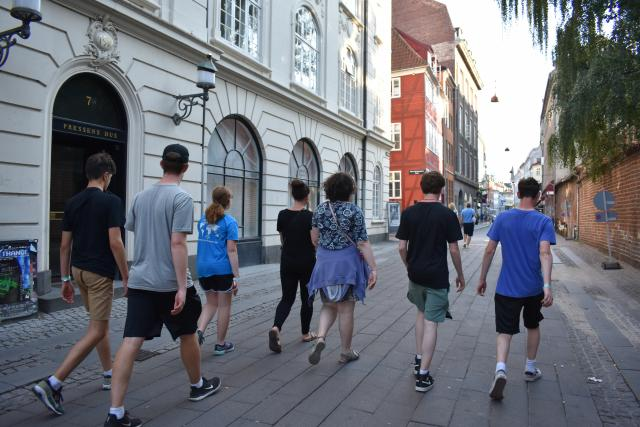 Teenage travelers walk through Gamla Stan during summer youth travel program in Scandinavia