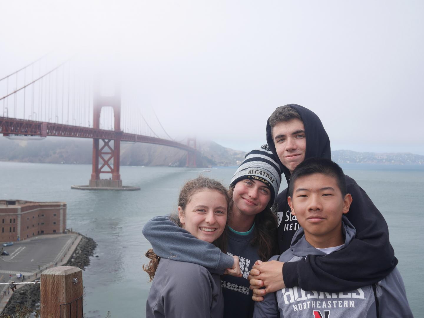 Friends pose for a photo in front of the Golden Gate Bridge on their summer teen tour of San Francisco, California.