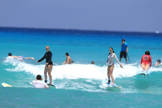 Teens learn how to surf on their summer travel program in North America.