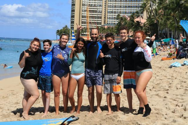 Group of teens learns how to surf on their summer travel program in Hawaii.
