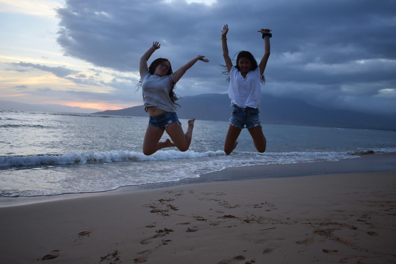 Friends jump on the beach in Hawaii during their summer teen tour.