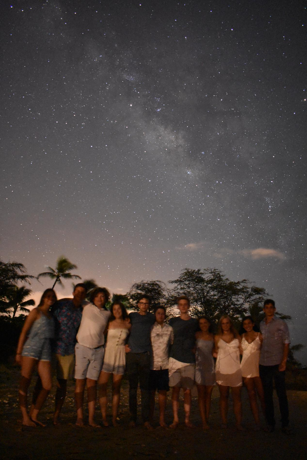 A group of students poses under the starry night sky on their teen tour of Hawaii and Australia.