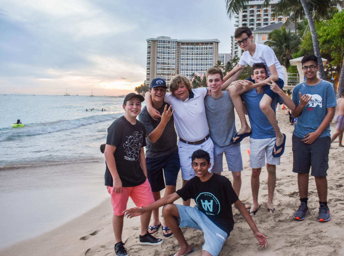 A group of friends poses for a photo on the beach during their teen tour of North America.