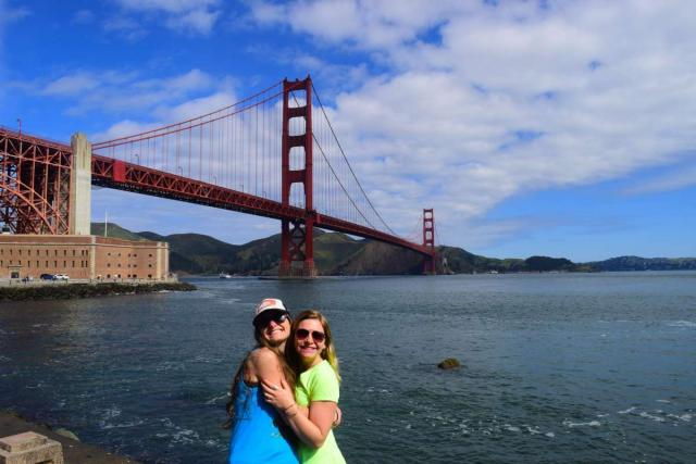 Two friends pose for a photo in front of the Golden Gate Bridge during their summer teen tour of San Francisco, California.