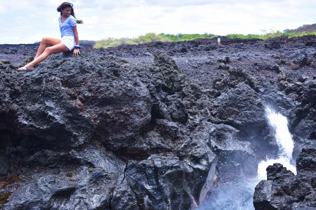A teen admires water from atop a lava rock during summer travel program in Hawaii.