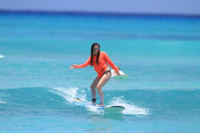 A teen learns how to surf during summer travel program in North America.
