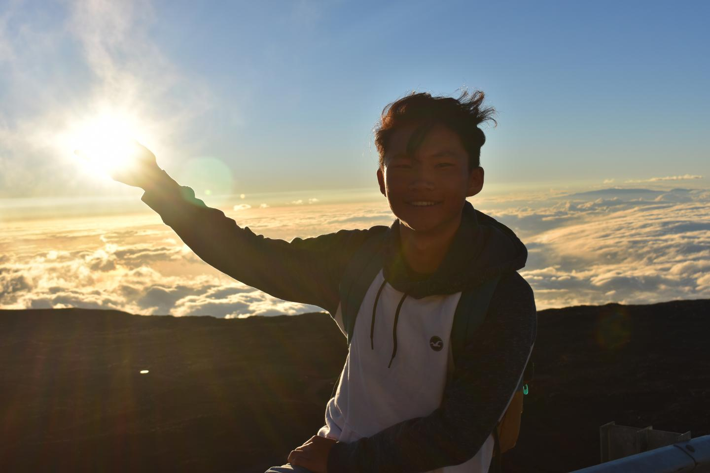 A teen catches the sunrise in Hawaii on summer travel program.