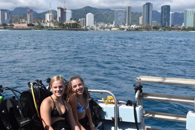 Teens pose for a photo on their boat ride past a city in Hawaii on their summer travel program.
