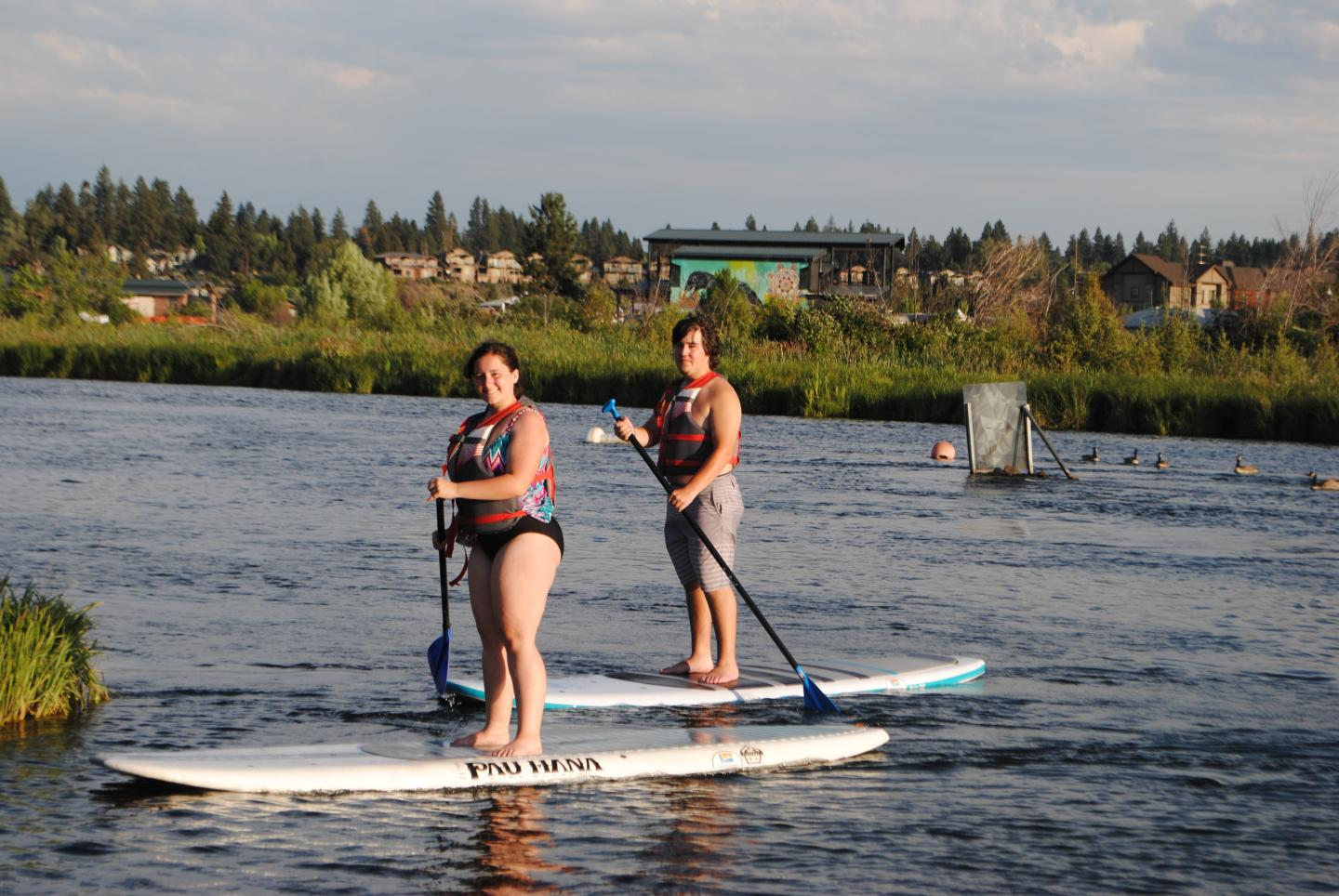 Students go stand-up paddle boarding on their summer teen tour of North America.
